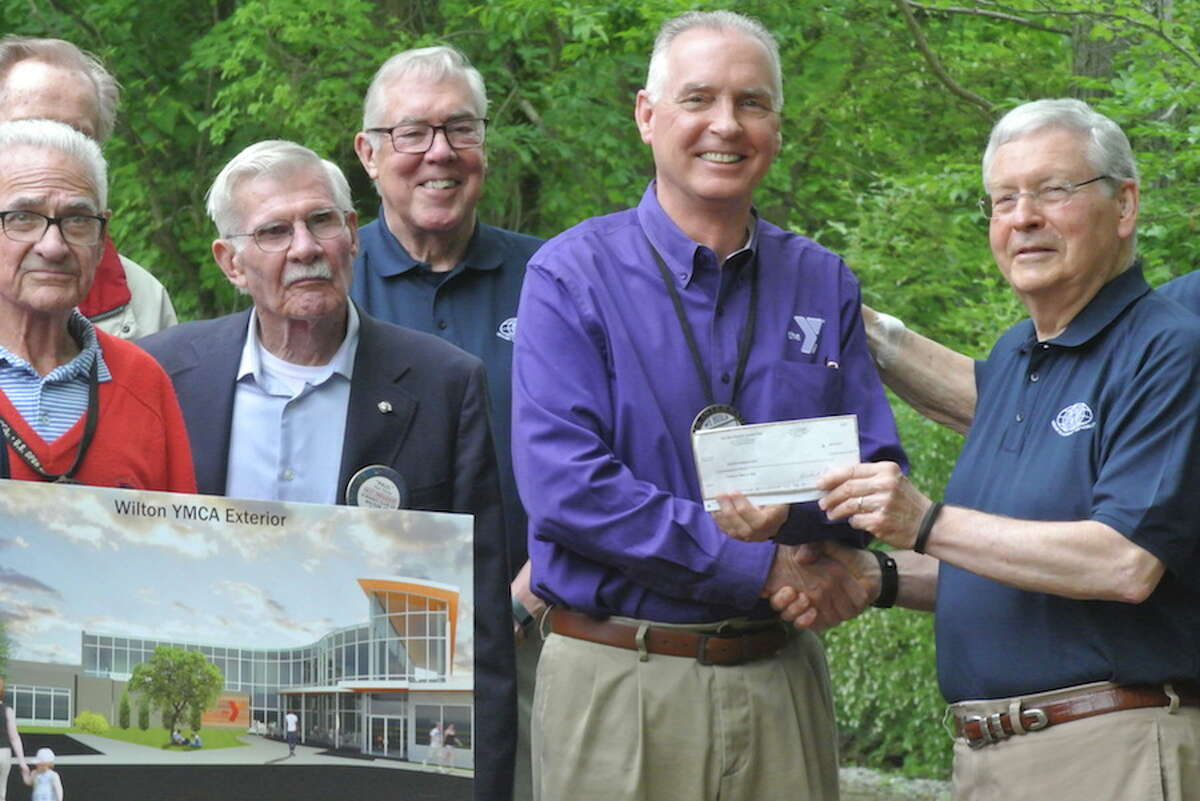 Kiwanians, from left, Jim Turnbull, Paul Young and Marty Clancy look on as Bob McDowell, executive director of the YMCA, accepts a check from John Kalamarides on behalf of the Wilton Kiwanis Club. - Tony Spinelli photo