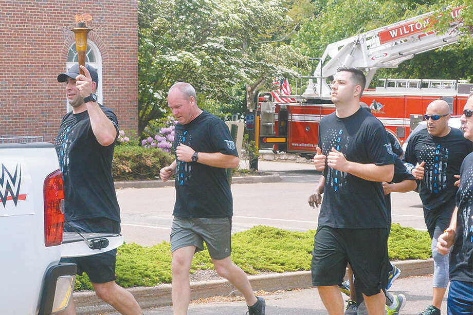 Police officers carry the Special Olympics torch through Wilton.