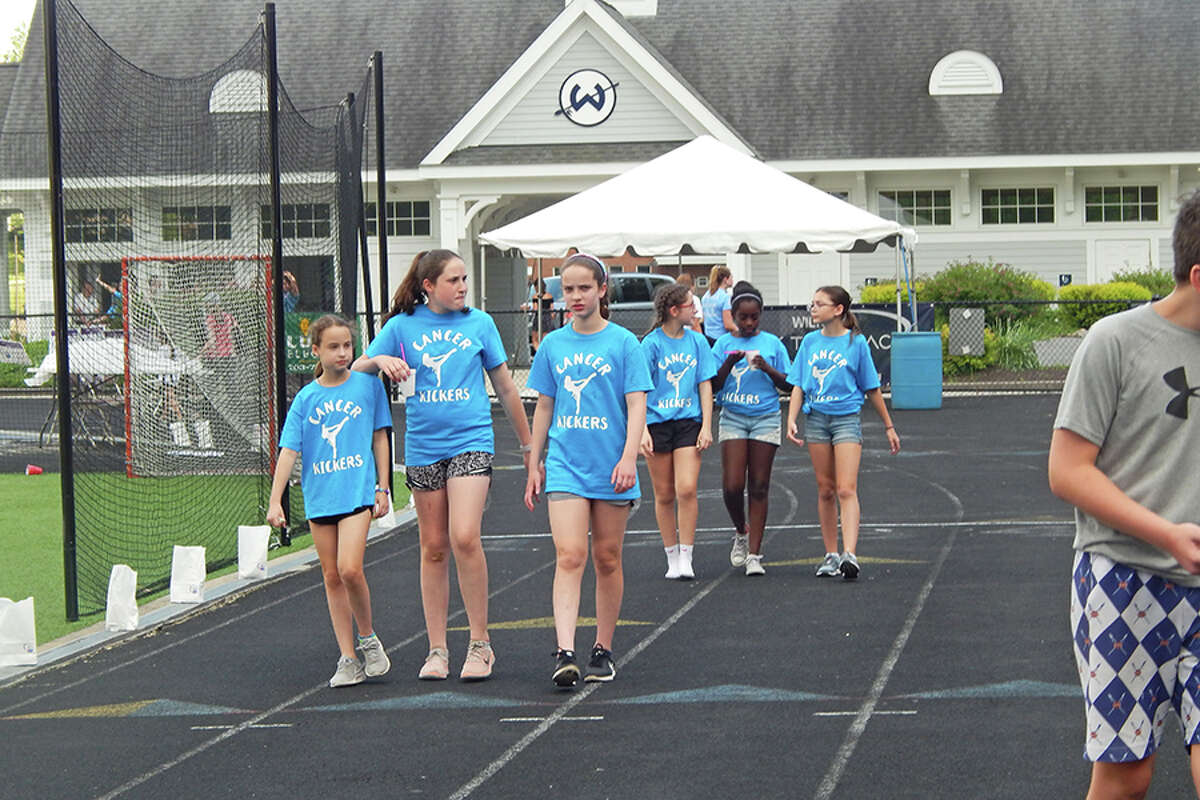 Members of the Cancer Kickers team walk the track at Wilton High School during this year's Wilton Relay for Life.