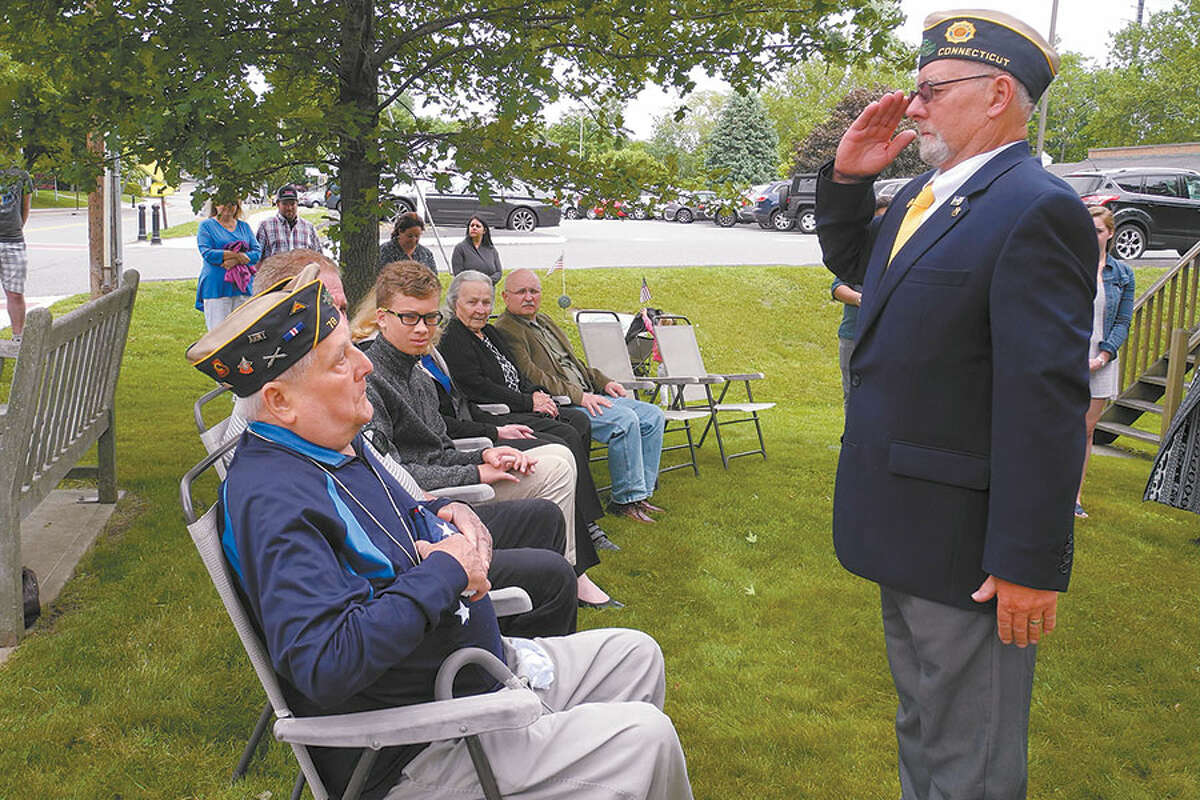 Post 86 Commander Don Hazzard salutes after handing a commemorative flag to Fred Whipple Sr.