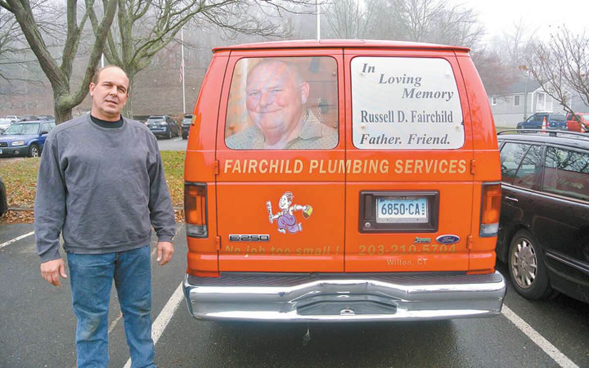 John Fairchild standing beside his business van, the back of which is decorated with memorial decals that remember his father, Russell D. Fairchild. Designs by A-to-Z Signs of Norwalk. - Hayden Turek photo