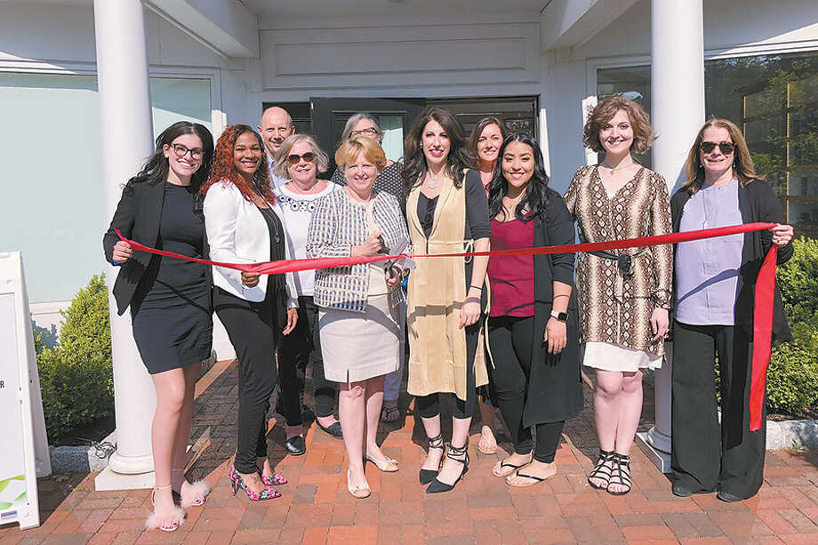 Celebrating the grand opening of the Eco Chic salon are, in front from left, stylists Elizabeth Murphy and Casey Eaton, First Selectwoman Lynne Vanderslice, salon owner Michele Maestri-Murphy, stylists Lucy Reyes and Ann Labine, and Susan Goldman, Chamber president. In back are Chamber members John DiCenzo, Judy White and Peg Koellmer, and stylist Liz Anderson. — Contributed photo