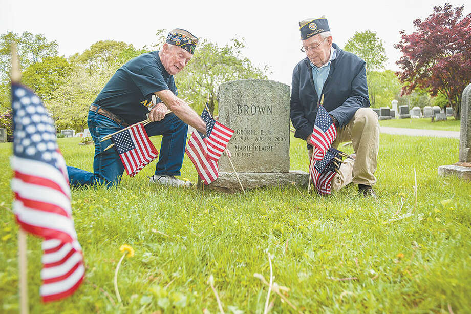 Air Force veteran Bing Ventres, left, and Judd Mott, a veteran of the Air National Guard of Connecticut, place flags at the graves of Wilton veterans in Hillside Cemetery. Both men served during the Korean War. Hillside will be the setting for a ceremony of remembrance at the end of the Memorial Day parade on Monday, May 28. — Bryan Haeffele photo / BryanHaeffele