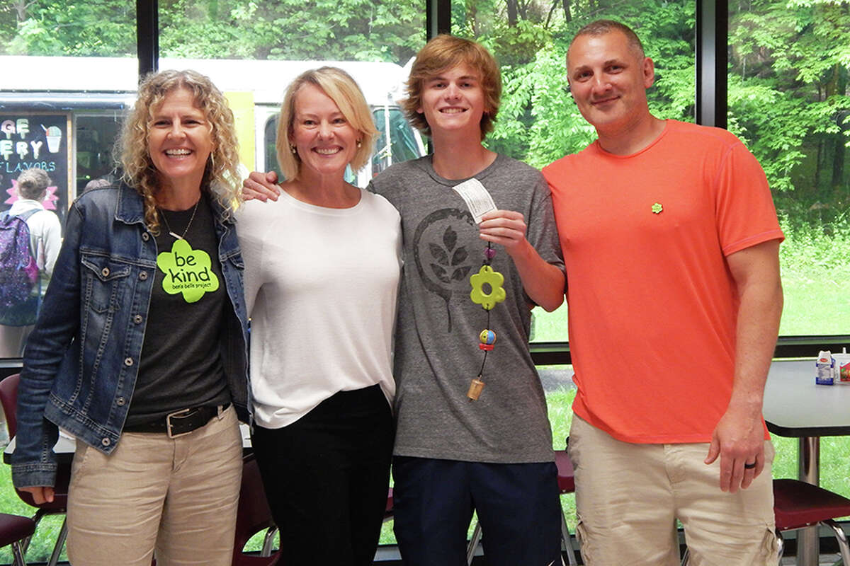 Tor Aronson, second from right, holds the Ben's Bell he was presented with May 23 at Wilton High School. He is pictured with, from left, Ben's Bells founder and executive director Jeannette Maré, his mother, Inger Sjogren; and Ben's Bell Project regional manager Cody Foss.