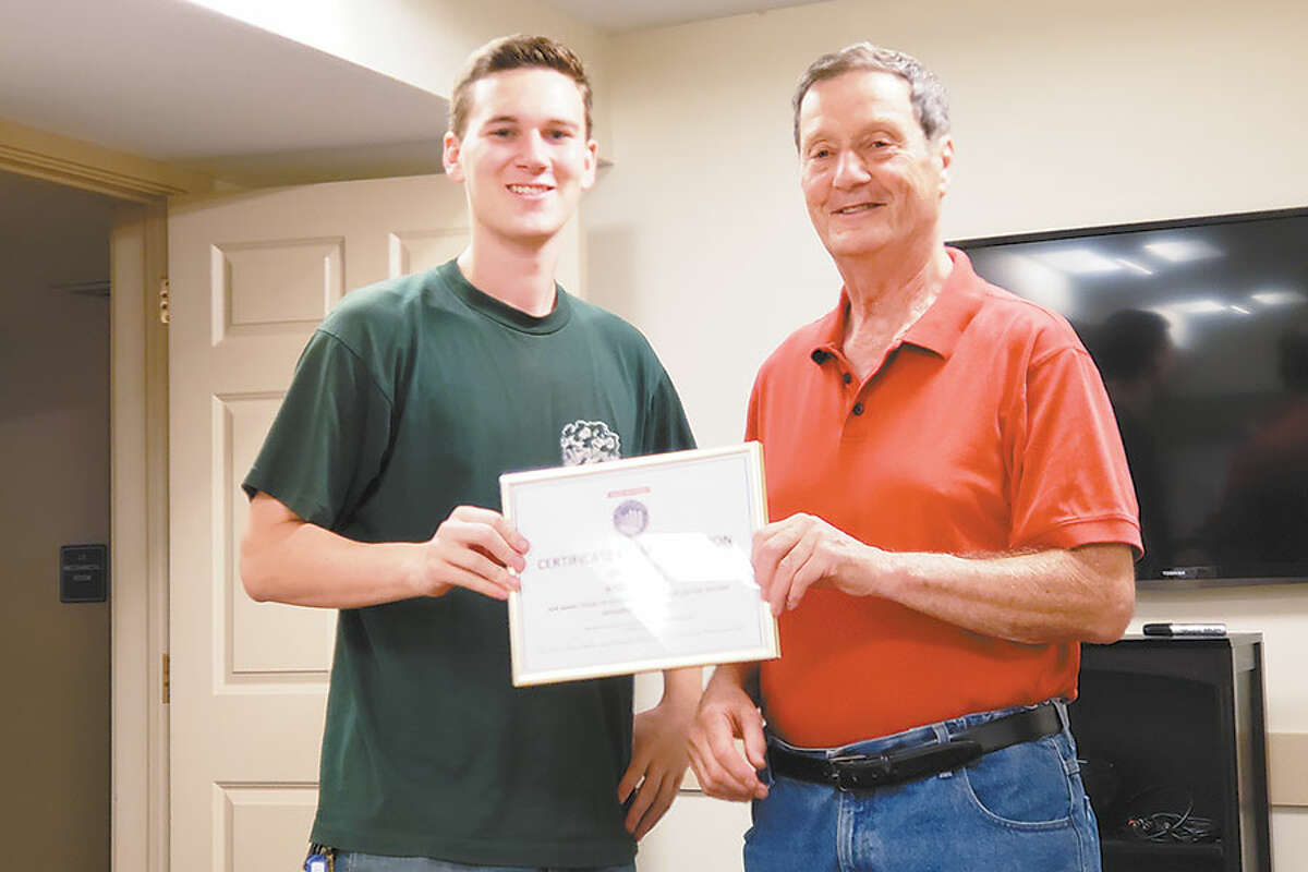 Parade chairman Jim Newton, right, presents the certificate of appreciation to Andrew Knapp's son, Andrew. The father could not be present for the ceremony. - Contributed photo