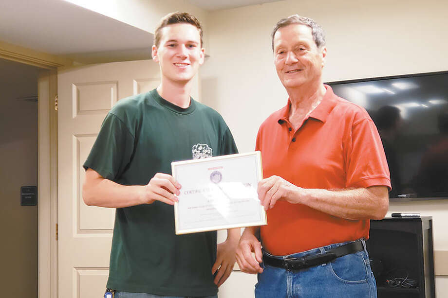 Parade chairman Jim Newton, right,  presents the certificate of appreciation to Andrew Knapp's son, Andrew. The father could not be present for the ceremony. — Contributed photo