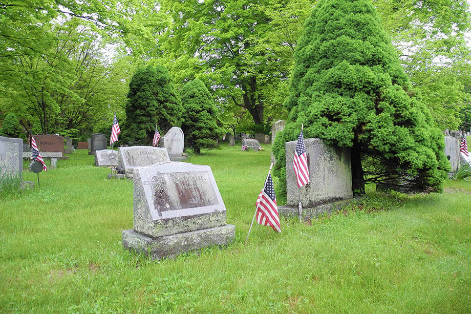 Flags decorate the graves of veterans at Hillside Cemetery, where a service of remembrance will take place at the conclusion of Monday's parade. — Jeannette Ross photo