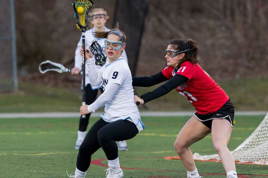 Sophia Sudano is guarded by New Canaan's Natalie Lopez during the the Wilton girls lacrosse team's loss to the Rams back on April 5. — GretchenMcMahonPhotography.com