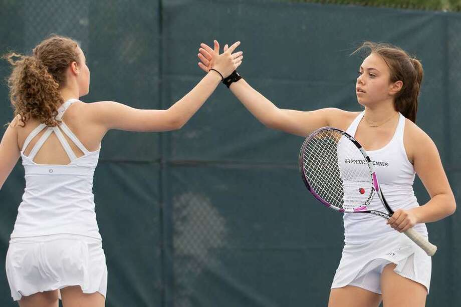 Grace Cahill (right) and Gerri Fox celebrate a point during their second doubles match last week. — GretchenMcMahonPhotography.com