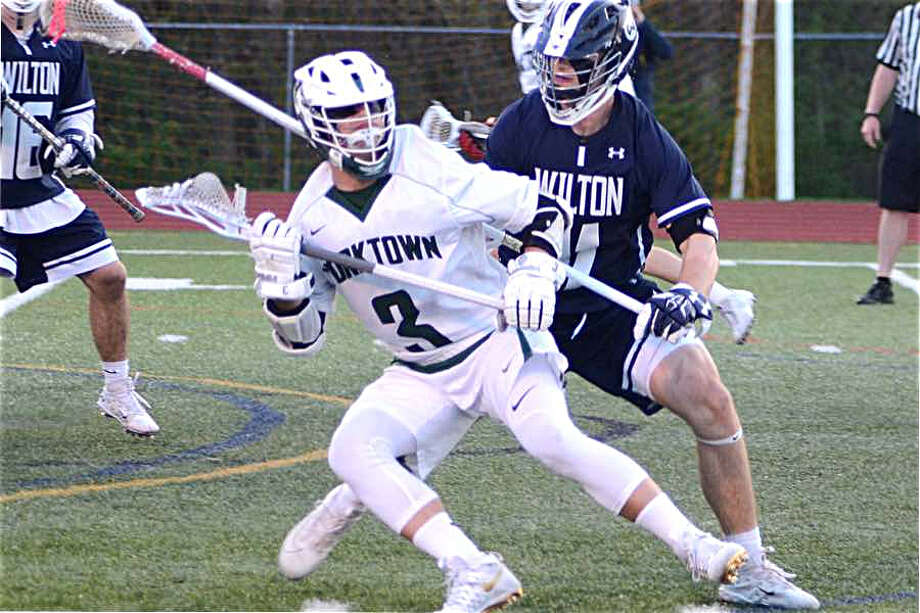 Ryan Schriber holds off Yorktown's Jamison Embury during the Wilton High boys lacrosse team's loss on Tuesday night in Yorktown. — J.B. Cozens photo