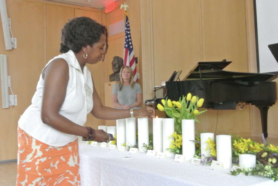 Adrienne Reedy lights the unity candle at Thursday's service commemorating National Prayer Day. Joan Wallace, in the background, sang We Are One during the service. — Jeannette Ross photo