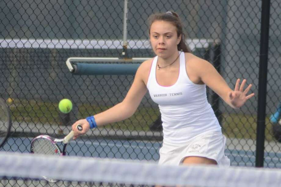 Grace Cahill reaches for a ball during Wilton girls tennis doubles action from earlier this season. — J.B. Cozens photo