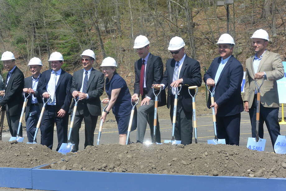 First Selectwoman Lynne Vanderslice and U.S. Rep Jim Himes, center, dig with shovels among others at the groundbreaking for ASML's parking garage. —Tony Spinelli photo.