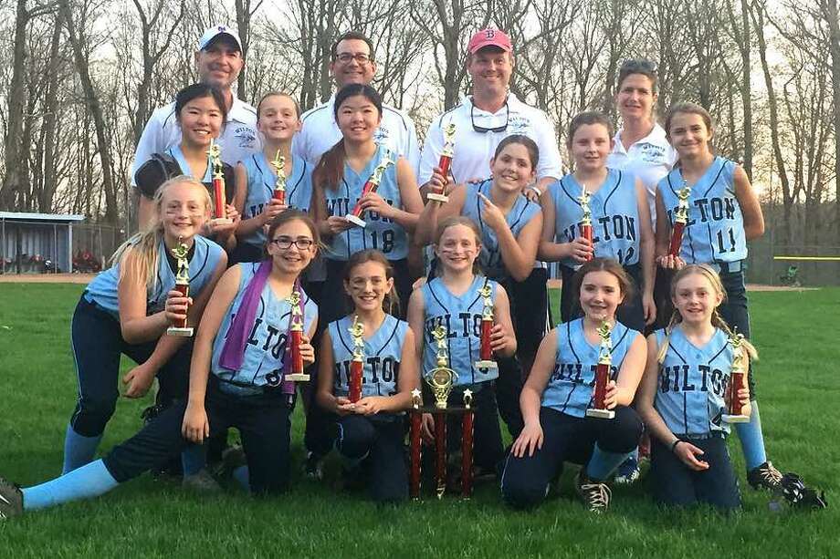 The Wilton Blue 10U softball team after winning the Sunrise Cottage Tournament in Ridgefield on Wednesday. From the left, front row: Ava Gaudio, Kaitlin Feldman, Sophia Viggiano, Emma van Heyst, Grace Couch and Allison Rayment; middle row: Ellie Qudeen, Sarah Morris, Grace Qudeen, Annie McMahon, Kayleigh Whitters and Sofia Samai; and back row: coaches Aaron Feldman, Tom Viggiano, Matt McMahon and Amanda Samai. — Beth Anne McMahon photo