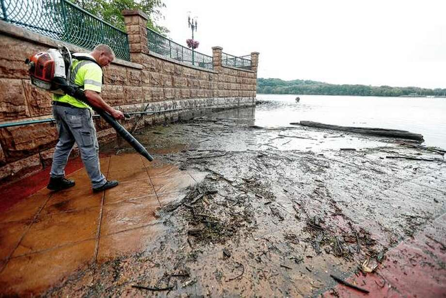 Matt Cooper, a city worker in Dubuque, Iowa, cleans off an area of American Trust River's Edge Plaza on Wednesday in Dubuque after high water levels of the Mississippi River left large amounts of debris and mud. Photo: Dave Kettering | Telegraph Herald Via AP