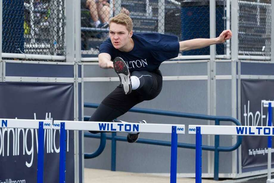 Charlie Golbourn clears the barrier in the 110-meter hurdles during Wilton track and field action. — GretchenMcMahonPhotography.com