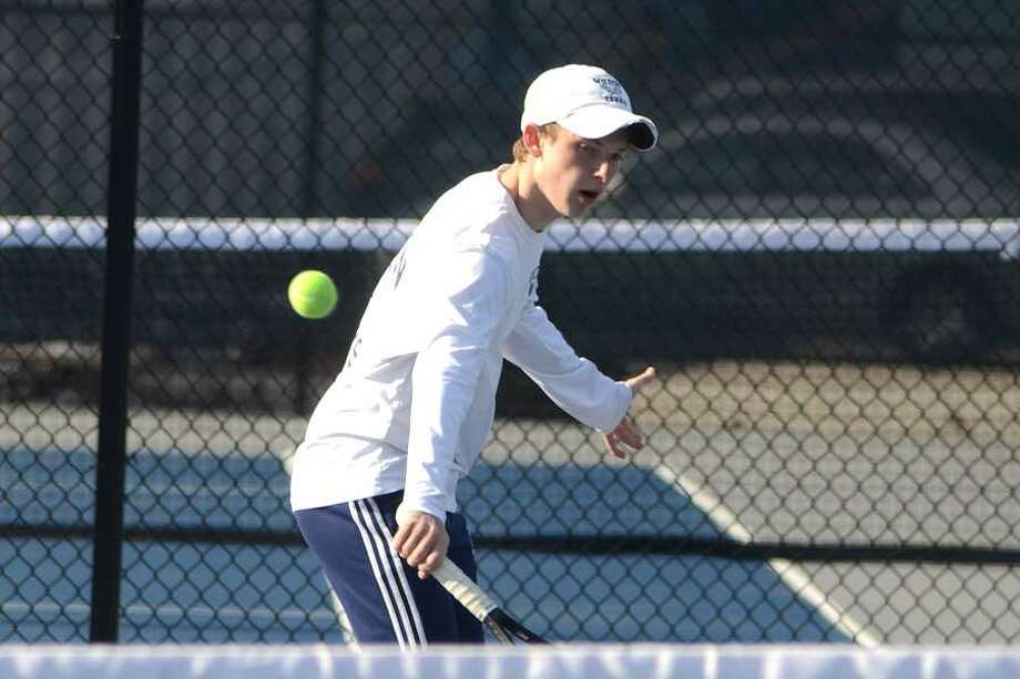 First doubles player Henry Murphy plays a ball at the net during Wilton boys tennis action earlier this season. — J.B. Cozens photo