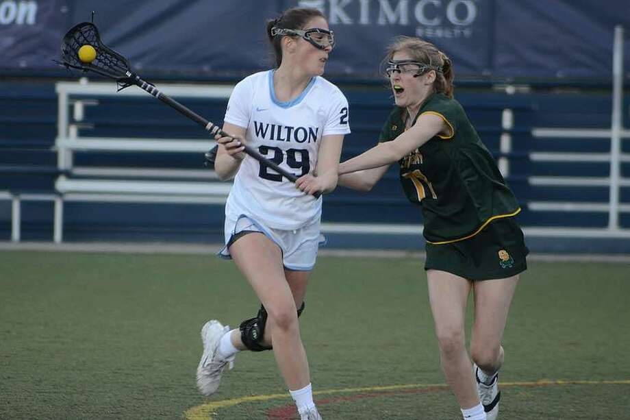 Eva Greco is guarded by Greenwich Academy's Emmeline Kelley during the Wilton girls lacrosse team's loss to the Gators on Thursday night at home. — J.B. Cozens photo
