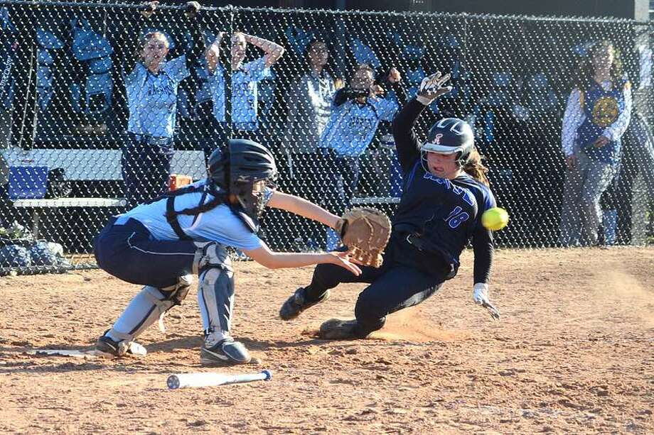 Darien's Stefani Gentile slides into home while Wilton catcher Maya Farrell awaits the throw, during the 11th inning of Thursday's softball team in Wilton. — J.B. Cozens photo