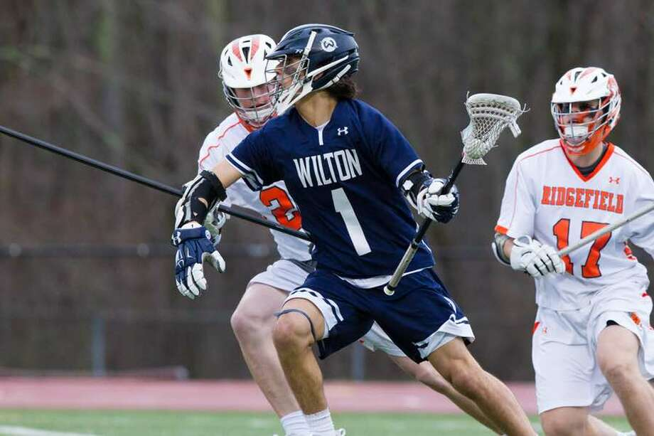 Dean DiNanno goes on the attack during the Wilton boys lacrosse team's game on Thursday night at Ridgefield. — GretchenMcMahonPhotography.com