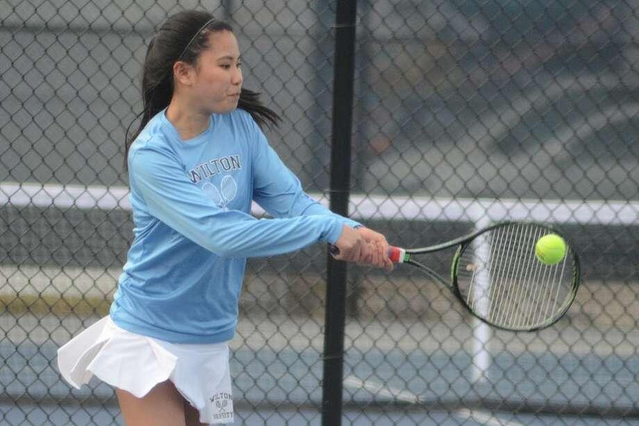 Amber Li hits a backhand shot for the Wilton High girls tennis team in a recent match at home. — J.B. Cozens photo