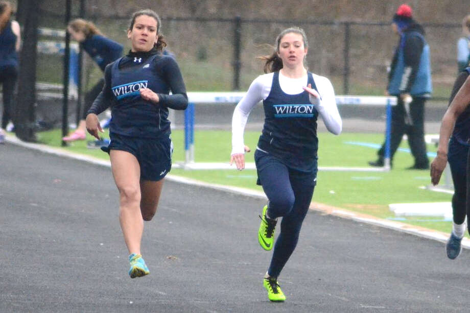 Claudia Nanez (left) and Tatem Kelly power down the track in the 100 meters at the Wilton track and field teams' meet on Tuesday at home. — J.B. Cozens photo