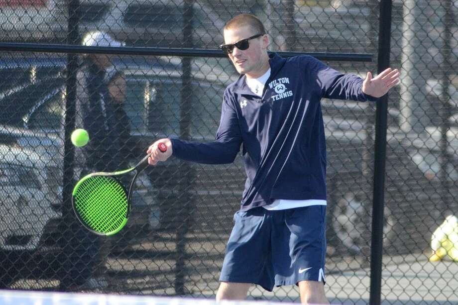 Owen McKessy plays a ball during the Wilton High boys tennis team's match on Thursday at home against New Canaan. — J.B. Cozens photo