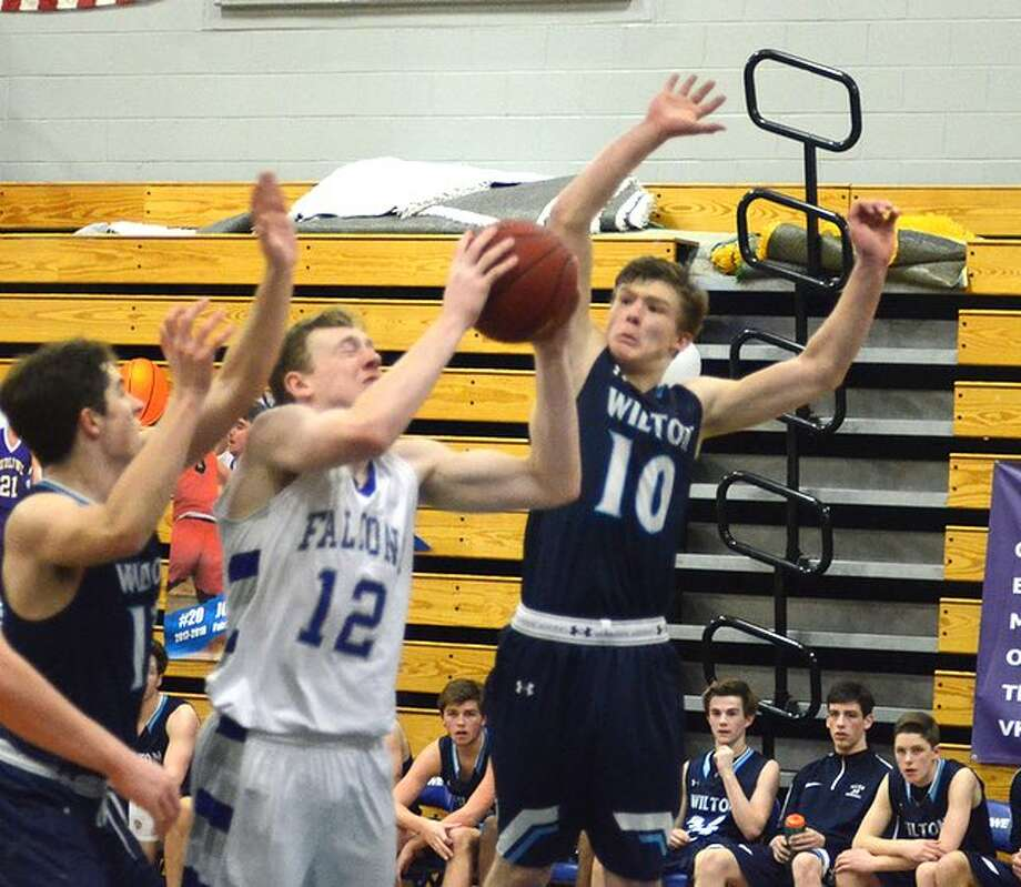 Kyle Phillips goes up to block a shot by Fairfield Ludlowe's Justin Schiller during the Wilton boys basketball team's win on Wednesday night. — J.B. Cozens photo