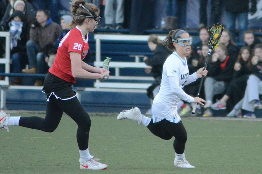 Sophia Sudano tries to elude New Canaan's Leigh Charlton during the Wilton girls lacrosse team's 6-4 loss to the Rams on Thursday in Wilton. — J.B. Cozens photo