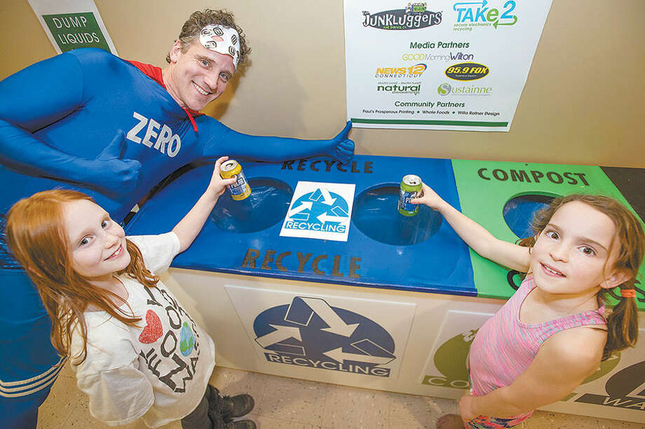 Eight-year-old Maryn Priest and 9-year-old Grace Jeanes help Captain Zero save the planet by recycling cans at the Zero Waste Faire on Sunday at the Wilton High School Fieldhouse. The event featured interactive exhibits top help residents move toward a zero-waste community. / BryanHaeffele