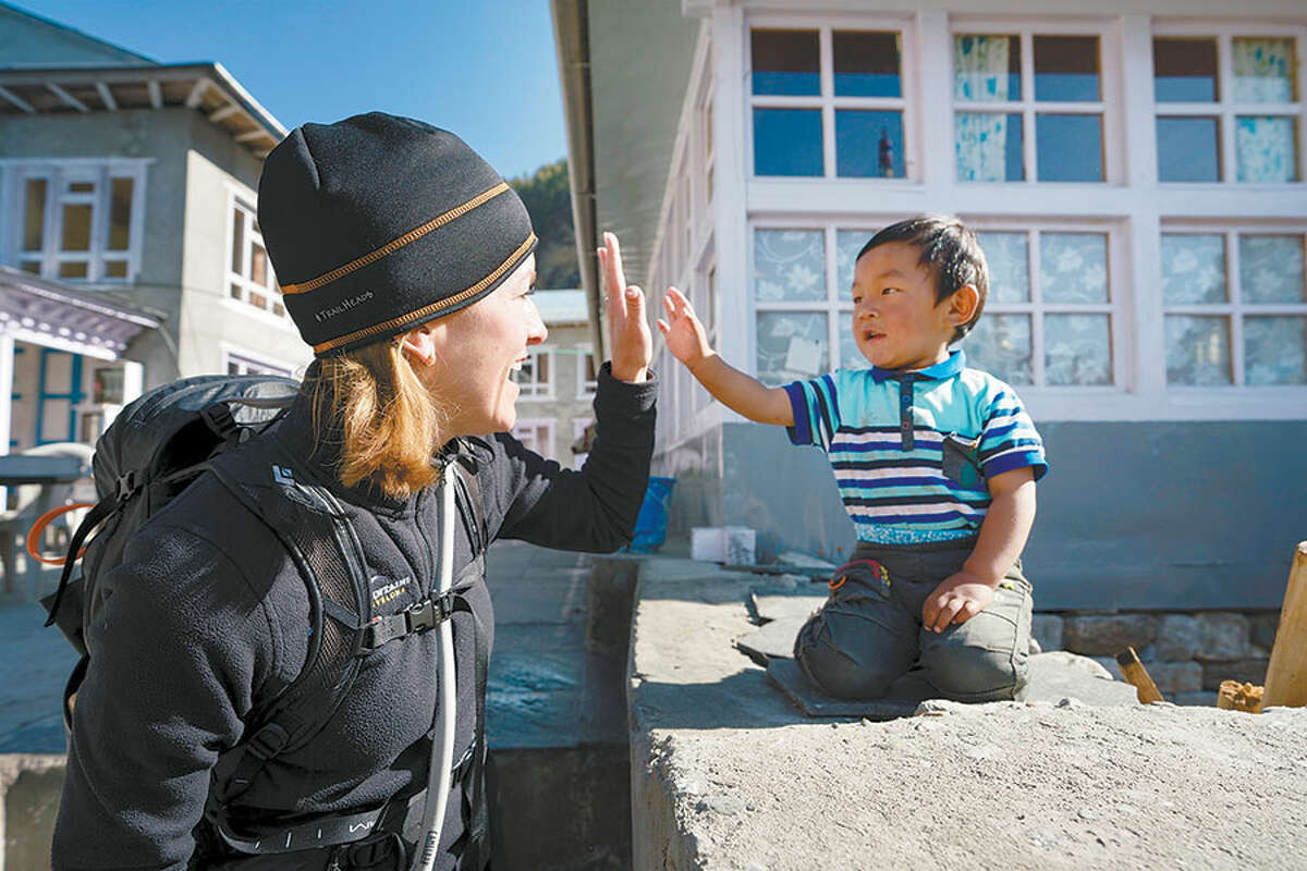 Annamarie Kealy exchanges a high five with a small boy in the Nepalese town of Phakding.