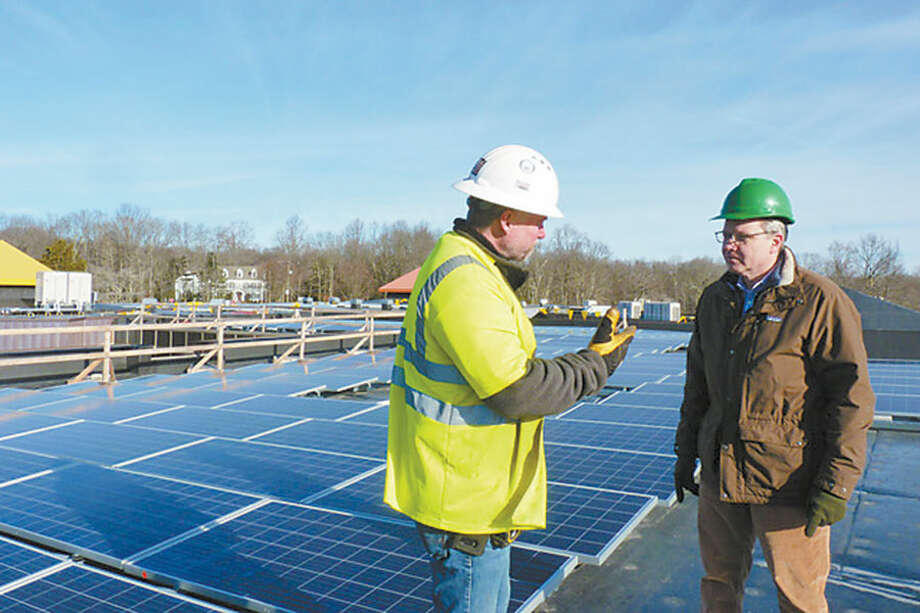 Peter Tevendale of Windward Solar, left, and Mark Robbins, founder and president of MHR Development, discuss the solar panel array on the roof of Miller-Driscoll School. — Contributed photo