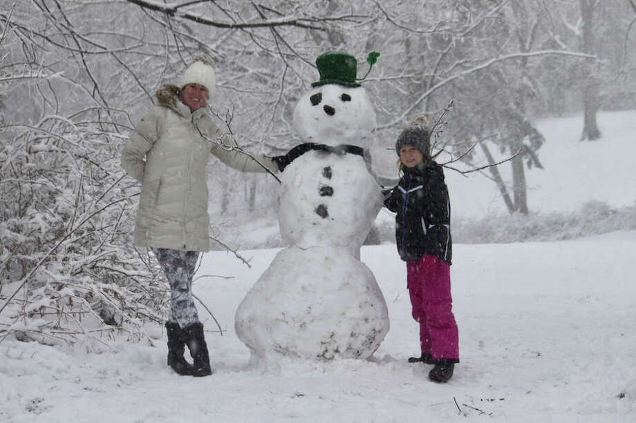 Kathryn Groves and her daughter Schuyler take advantage of the snow day and make a St. Patrick's Day snowman. — Brooks Garis photo