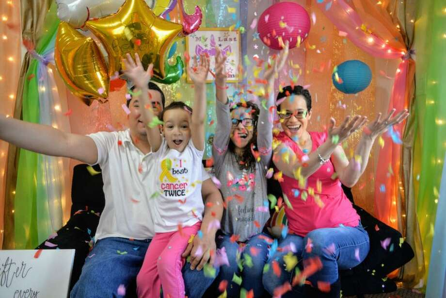 The family celebrates 5-year-old Victoria Diaz's last chemotherapy treatment in April. From left, Frank Diaz, Victoria, Kiara and Emily Padilla. —Laura St John Photography