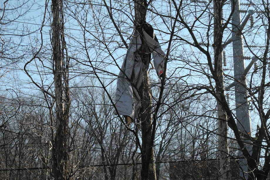 A tarp is caught in the trees along the Norwalk River. A town-wide effort to remove garbage from along the river's banks and town roadways is planned for May 4. — Jeannette Ross/Hearst Connecticut Media