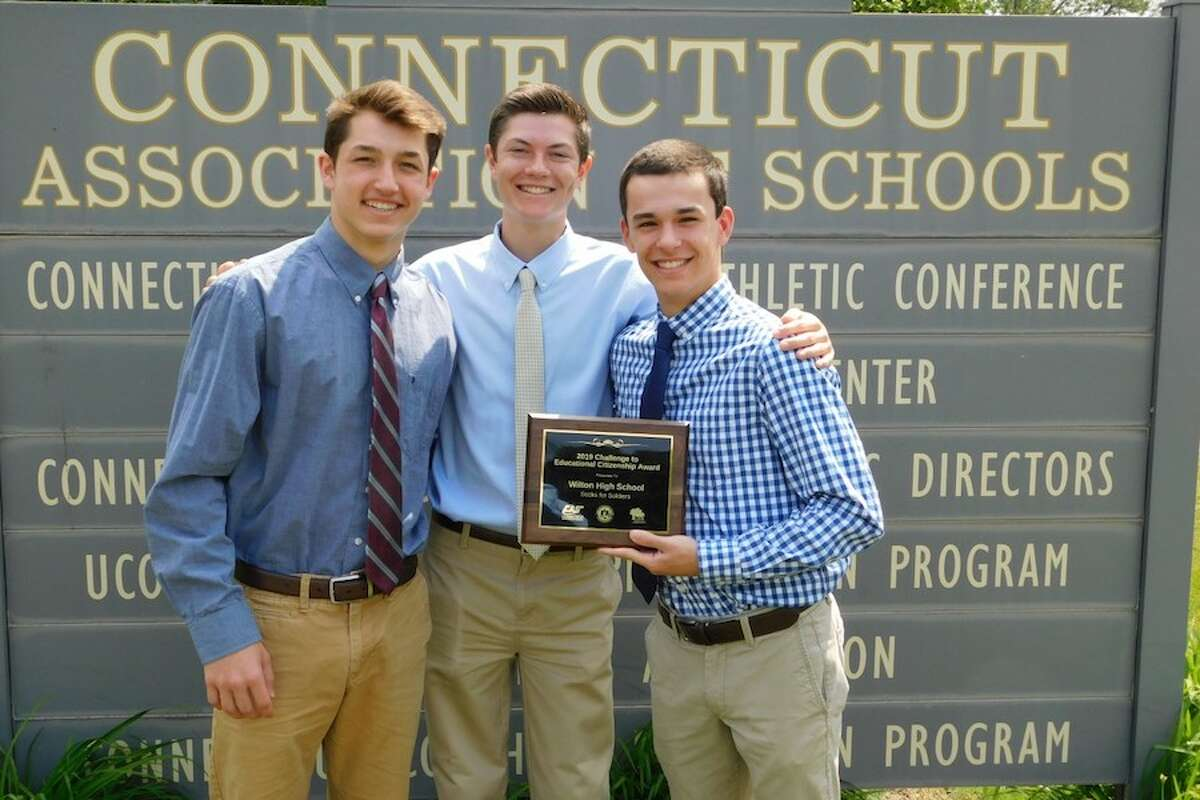From left, Jake Zeyher, Kace Stewart, and Connor Burke are at the Connecticut Association of Schools in Cheshire to receive an award for Sock for Soldiers program on June 5.
