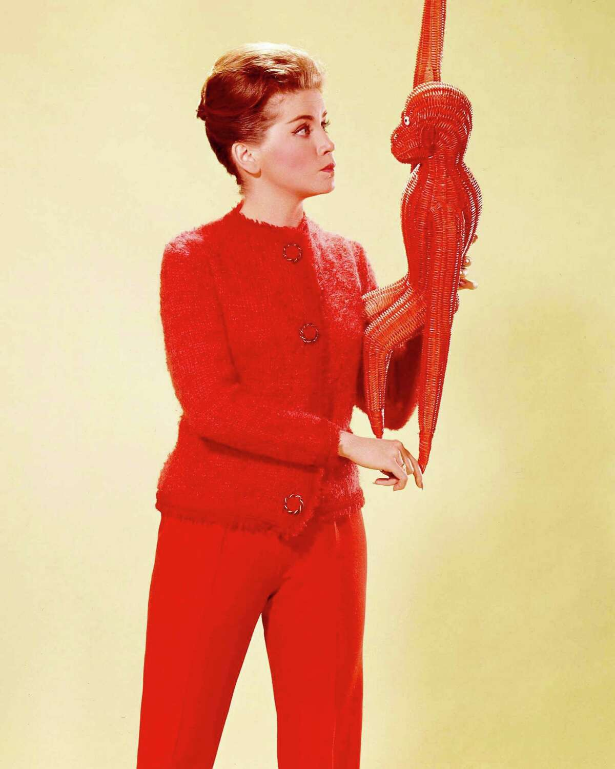Dolores Hart, US actress, wearing red trousers and a knitted red cardigan, and holding a red wicker monkey, circa 1960. (Photo by Silver Screen Collection/Getty Images)