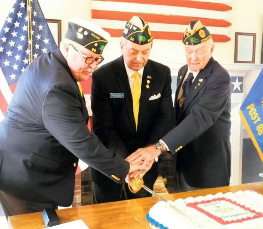 From left, Tom Moore, Bill Glass and Bing Ventres use a ceremonial sword to cut a cake celebrating the 100th anniversary of the American Legion at Post 86. — Jeannette Ross/Hearst Connecticut Media