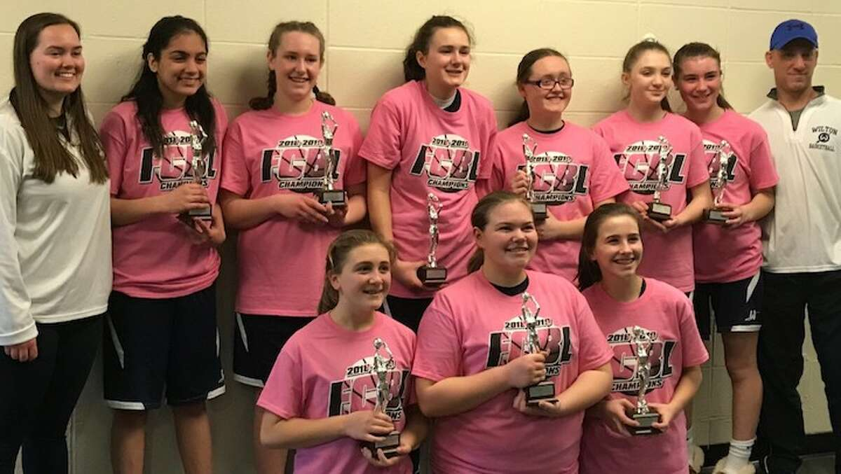 The Wilton 7th/8th grade girls team celebrates after winning a Fairfield County Basketball League title.