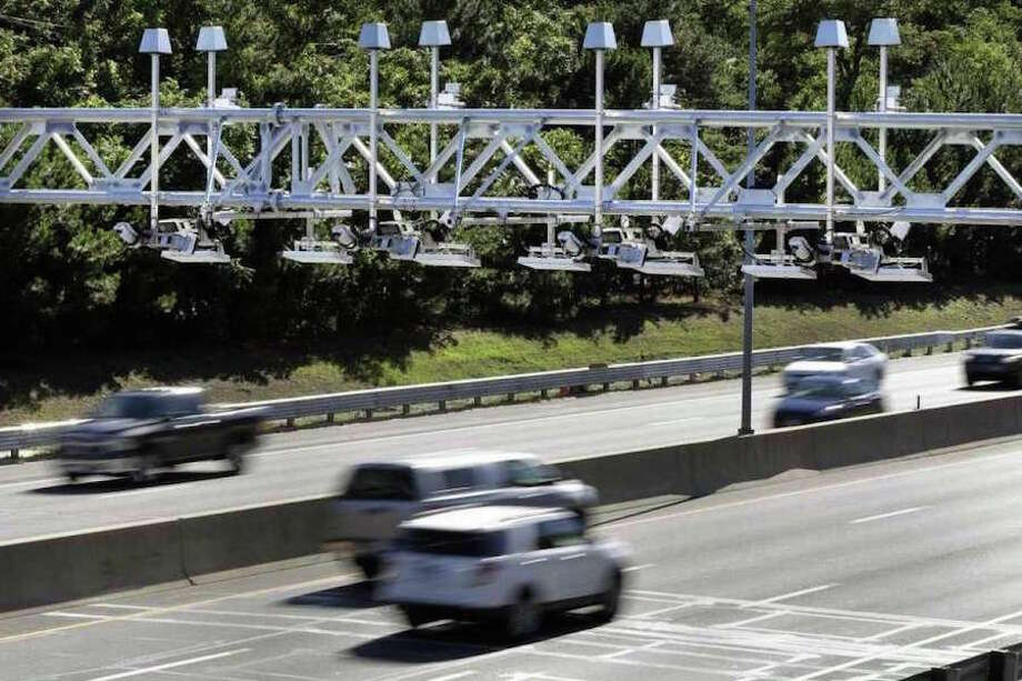 In a 2016 file photo, cars drove under electronic toll gantries on the Mass Pike. (AP Photo /Elise Amendola, File) /