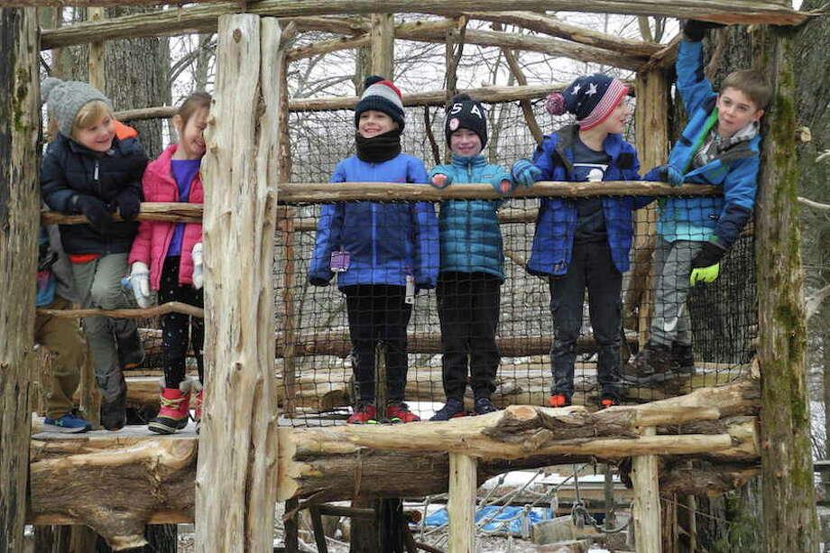 From left, Killian Lehman, Adeline Hatch, Harrison Cain, Finney Leonard, Henry Rondeau, and Xander Baronak enjoy the new playground at Woodcock Nature Center in Wilton on Feb. 27.