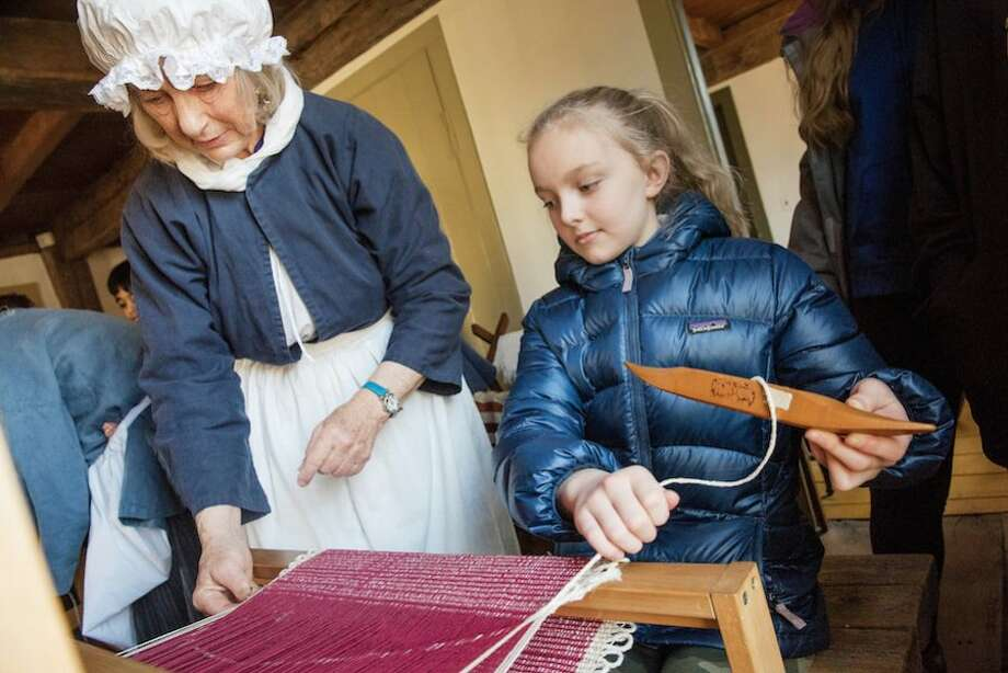 Judy Wald demonstrates weaving to Bella Albers.