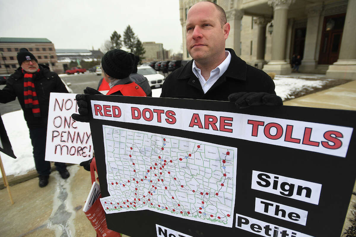 Patrick Sasser, of Stamford, and protestors from the group No Tolls CT, hold signs outside the Capitol in Hartford on Feb. 20. Gov. Lamont has proposed tolls on state highways to pay for transportation improvements.