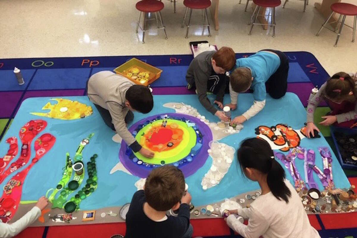 Miller-Driscoll students work on a mural using recyclable materials. - Contributed photo