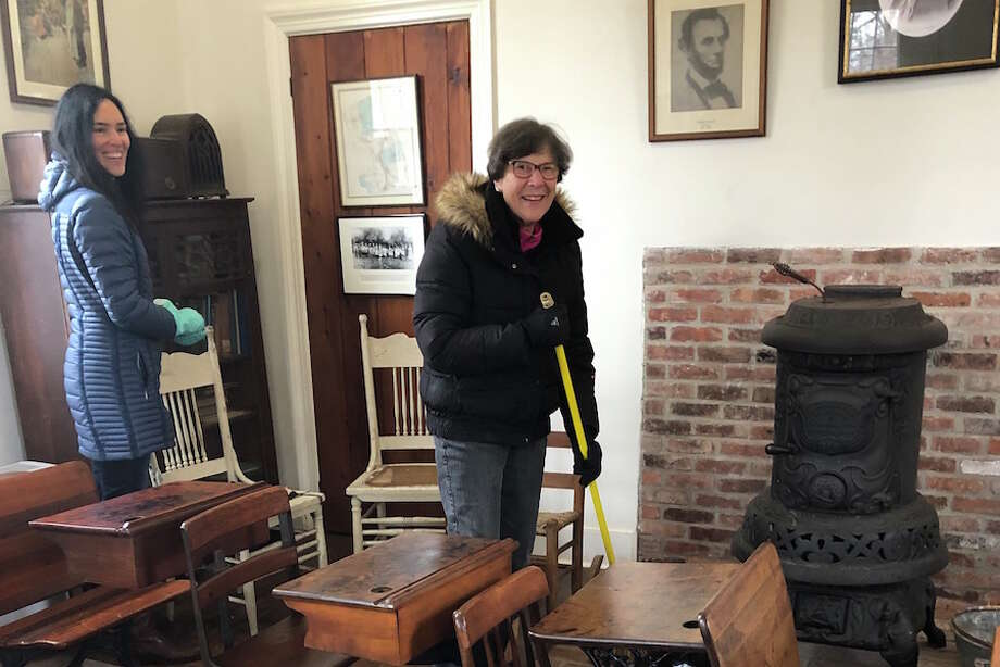 Chrissy Silva, left, and Linda Schmidt, chair of the Hurlbutt Street Schoolhouse Committee, clean up the schoolhouse in preparation for visits by Wilton students. — Contributed photo
