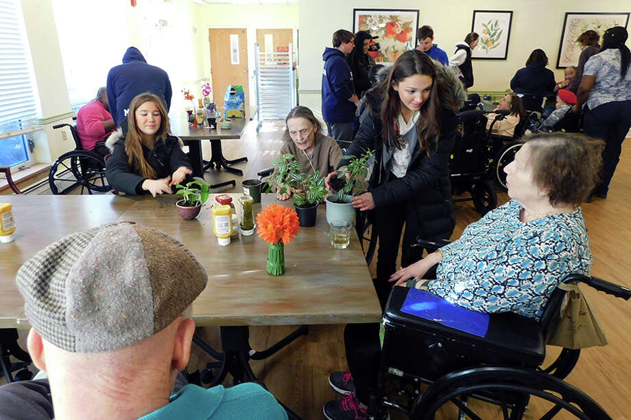 Wilton High School students help Wilton Meadows residents Catherine Hrozenchik and Patricia Reir plant during the Jan. 14 workshop. / NikonCoolpix