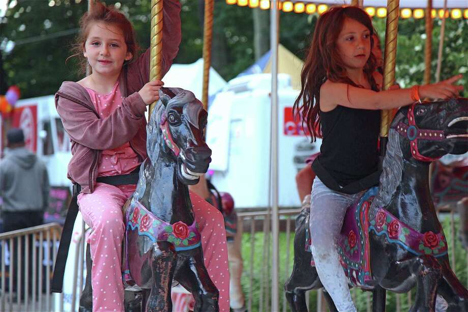 Lana Murphy, 8, left, and Riley Appel, 7, both of Westport, take a spin on the merry-go-round at the Yankee Doodle Fair on Thursday, June 13, 2019, in Westport, Conn. Photo: Jarret Liotta / For Hearst Connecticut Media / Westport News Freelance