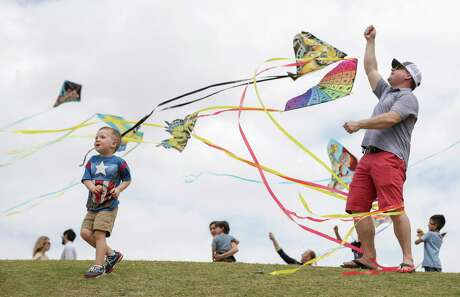 Mase Meeks, 3, left, chases a kite his dad, Evan Meeks, is flying during the 6th annual Hermann Park Conservancy Kite Festival at Hermann Park on Sunday, March 24, 2019, in Houston.