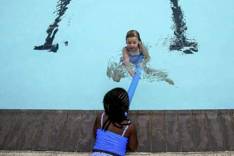 Meadow Ferguson, 3, helps to pull Ashlen Lengefeld, 5, to the edge of the pool at the Foster Family YMCA during a swimming safety and drawing prevention clinic to show ways parents and children can help other children in need Wednesday, May 25, 2016 in Houston. The YMCA of Greater Houston will be offering free swim ability assessments on May 28 to help parents get a better idea of how their children perform in the water. ( Michael Ciaglo / Houston Chronicle )