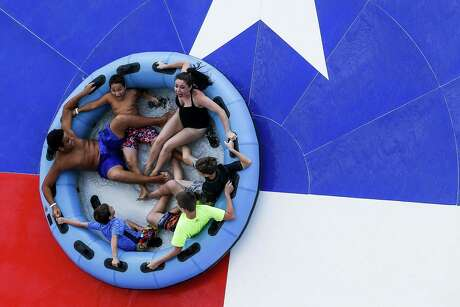 People laugh and scream as they reach the star of The Typhoon slide at Typhoon Texas where the water park is celebrating Christmas in July all week Wednesday July 25, 2018 in Katy. (Michael Ciaglo / Houston Chronicle)